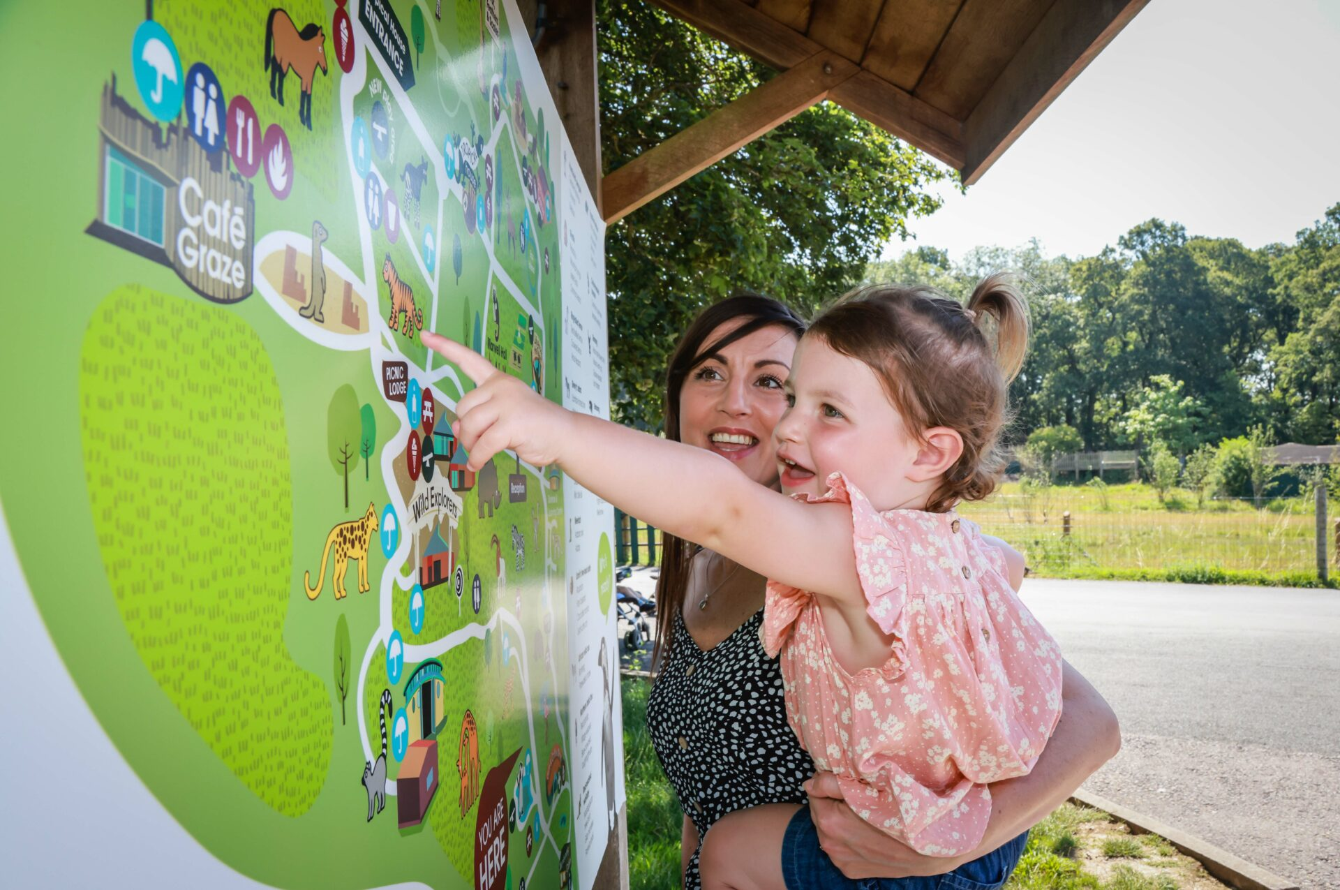 Girl with mother pointing at Map